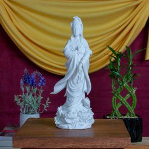 Estatua Kuan Yin parada sobre flor de loto